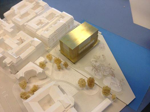 foto på guldglänsande modell med vita omgivande hus